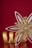 Christmas holiday snowflake and silver ribbon on dark red background. Xmas holiday theme Royalty Free Stock Photography