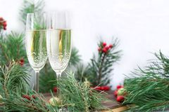 Christmas holiday still life, champaign, pine branches, red berries. Christmas and New Year seasonal composition with pine tree branches, two glasses of royalty free stock photography