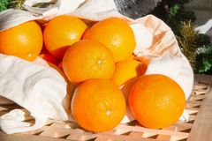 Christmas holiday still life with close up fresh raw oranges rolling out of the shopping bag. On Christmas tree background Royalty Free Stock Photos