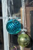 Christmas holiday storefront window display ball ornaments. Christmas holiday window rustic display with vintage metal painted ironwork gate and hanging ball stock image