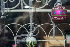 Christmas holiday storefront window display ball ornaments. Christmas holiday window rustic display with vintage metal painted ironwork gate and hanging ball stock photo