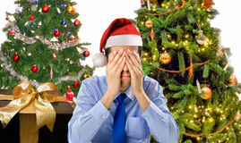 Christmas holiday stress. Stressed man is shopping gifts for christmas with red santa hat angry and distressed Royalty Free Stock Photo
