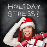 Christmas holiday stress - stressed shopping gifts. Christmas holiday stress. Stressed woman shopping for gifts holding christmas presents wearing red santa hat royalty free stock photo