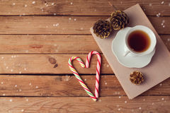 Christmas holiday tea cup on old books with love shaped candy on wooden table with copy space