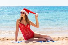 Christmas holiday vacation at the beach. girl in santa hat on the sea royalty free stock image