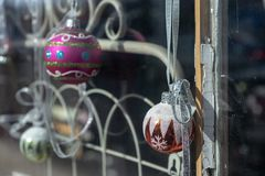 Christmas holiday storefront window display ball ornaments. Christmas holiday window rustic display with vintage metal painted ironwork gate and hanging ball royalty free stock photos