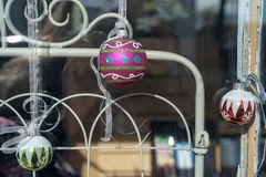 Christmas holiday storefront window display ball ornaments. Christmas holiday window rustic display with vintage metal painted ironwork gate and hanging ball royalty free stock photography