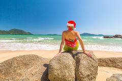 Christmas holidays on the beach. Beautiful, fashionable woman with red Santa Claus hat relaxing and catching tan on rocks in tropical Laem Ka Beach for the Stock Images