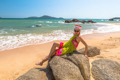Christmas holidays on the beach. Christmas in the tropical beach. Fashionable woman with red Santa Claus hat relaxing on rocks in Laem Ka Beach for the Christmas Royalty Free Stock Image