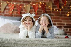 Christmas Holidays. Brother and sister lying on the bed in soft pajamas. Christmas Holidays. Brother and sister lying on bed in pajamas. The bedroom is Stock Photos