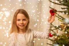 Happy girl in red dress decorating christmas tree stock photography
