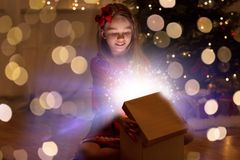 Smiling girl opening christmas gift at night stock images