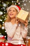 Smiling girl in santa hat with christmas gift stock images