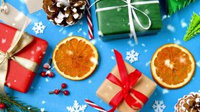 Gifts, fir branches, cones and dried orange slices. Christmas and holidays concept - gifts, fir branches, pinecones, candy cane decorations and dried orange stock video footage