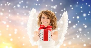 Teenage girl with angel wings and christmas gift. Christmas and holidays concept - happy young woman with angel wings holding gift box over snow background stock photography