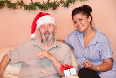 Christmas holidays elderly gift. Christmas holiday eldely man with grandchild and gift or present Royalty Free Stock Images