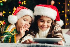 Christmas holidays at home. Happy children using tablet, playing. Online, having fun stock image