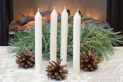Advent. Christmas. White wax candles, pine branches and pine cones on an openwork tablecloth on the background of an electric fire. Christmas holidays. Interior royalty free stock photography