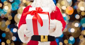 Close up of santa claus with christmas gift. Christmas, holidays and people concept - close up of santa claus with gift box over lights background Royalty Free Stock Image