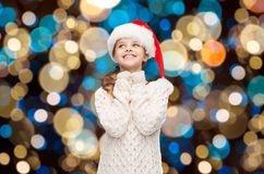 Dreaming girl in santa helper hat over lights Stock Photography