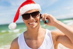 Man calling on smartphone on beach at christmas. Christmas, holidays and people concept - happy smiling young man in santa hat and sunglasses calling on Stock Images