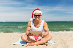 Happy man with tablet pc on beach at christmas. Christmas, holidays and people concept - happy smiling young man in santa hat with tablet pc computer sunbathing Stock Photography