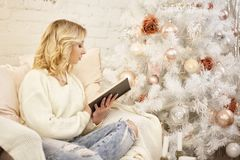 Christmas, holidays and people concept - happy young woman reading book at home royalty free stock image