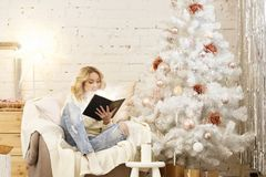 Christmas, holidays and people concept - happy young woman reading book at home stock photography