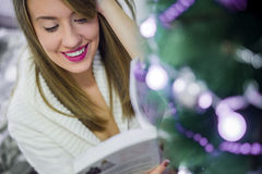 Christmas, holidays and people concept - happy young woman reading book at home. Stock Images