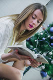 christmas, holidays and people concept - happy young woman reading book at home. Happy beautiful woman with make-up Stock Photo