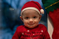 Christmas, holidays and people concept - little baby boy in santa hat stock photography