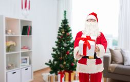 Santa claus with christmas gift at home. Christmas, holidays and people concept - man in costume of santa claus with gift box over home room background Stock Image