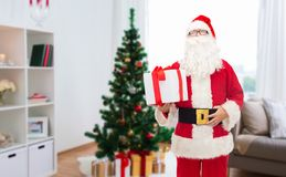 Santa claus with christmas gift at home. Christmas, holidays and people concept - man in costume of santa claus with gift box over home room background Royalty Free Stock Photos