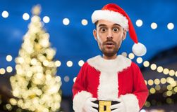 Man in santa claus costume over christmas lights Royalty Free Stock Images