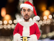 Man in santa claus costume over christmas lights Royalty Free Stock Photography
