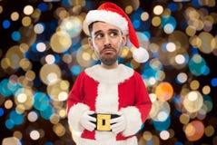 Sad man in santa costume over christmas lights Royalty Free Stock Photos