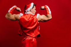 Christmas holidays. sexy strong santa claus wearing hat. Young muscular man. red background. Christmas holidays. sexy strong santa claus wearing hat. Young Royalty Free Stock Images