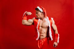 Christmas holidays. sexy strong santa claus wearing hat. Young muscular man. red background. Christmas holidays. sexy strong santa claus wearing hat. Young Stock Image
