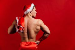 Christmas holidays. sexy strong santa claus wearing hat. Young muscular man. red background. Christmas holidays. sexy strong santa claus wearing hat. Young Royalty Free Stock Photos