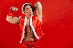 Christmas holidays. sexy strong santa claus wearing hat. Young muscular man. red background. Christmas holidays. sexy strong santa claus wearing hat. Young Stock Photography