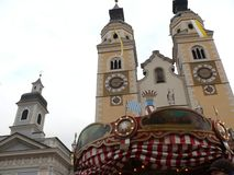 Merano, Trentino, Italy. 01/06/2011. Church in the village with a carousel. During the Christmas holidays the town is enriched with markets and rides stock image