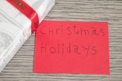 Christmas holidays write on a red paper with decorations royalty free stock photography