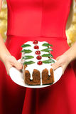 Christmas holly fruitcake kept in the hands of young woman Royalty Free Stock Photos