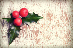 Christmas holly with red berries. On  wooden background Royalty Free Stock Photos