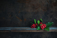 Christmas Holly. Twig. Christmas decoration with red berries placed on a wooden shelf royalty free stock images
