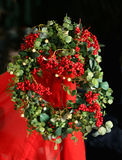 Christmas Holly Wreath. With berries and mistletoe hanging on red material Royalty Free Stock Photography