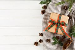 Christmas holydays presents on white wood table background. Scarf, xmas box, fir branch Royalty Free Stock Photos