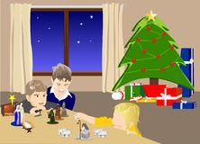 Christmas at home. Three children placing nativity figures on a table Stock Image