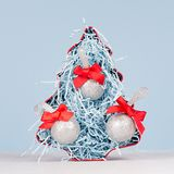 Christmas home decor - bright red decorative fir and silver balls with red silk bows on white and blue background, closeup, square royalty free stock photos