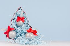 Christmas home decor - bright red decorative fir and silver balls with red silk bows on white and blue background, copy space. stock photos